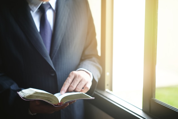 A business is reading the bible in the room.