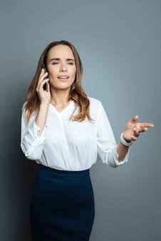 Деловые вопросы. хорошая профессиональная умная бизнесвумен держит свой телефон и обсуждает бизнес, разговаривая со своим собеседником