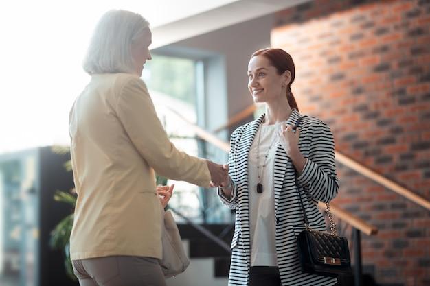 ビジネスの女性。ホールで彼女の隣に立っている彼女の先輩の同僚に挨拶するかっこいい若いビジネスレディ