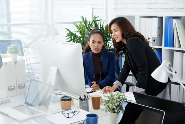 Business lady asking colleague to help her with making presentation for meeting of sales department