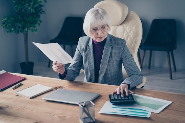 Бизнес-леди за столом работает на своем ноутбуке