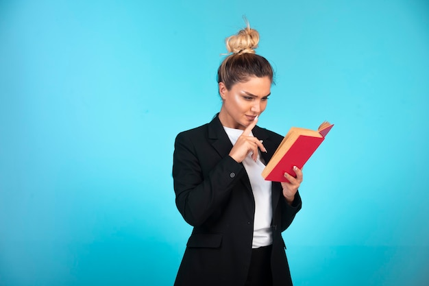 Business lady in black blazer with a red book and reading it.