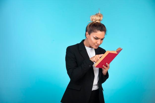 Signora di affari in giacca sportiva nera con un libro rosso e leggerlo.