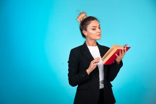 Signora di affari in giacca sportiva nera con un libro rosso che pensa e che legge.