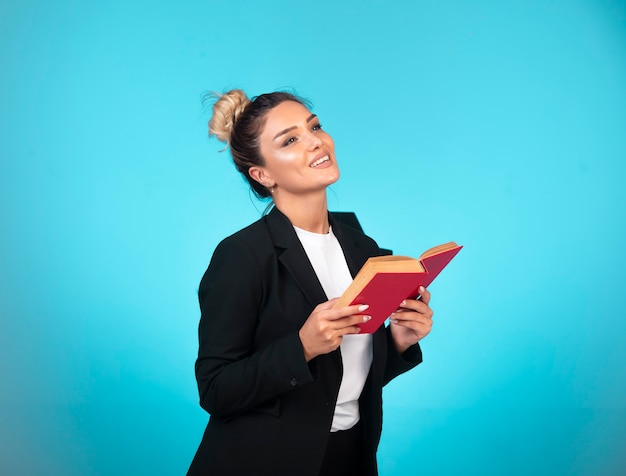 Business lady in black blazer with a red book thinking.