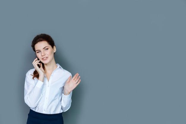 ビジネスレディ。仕事について話している間、自信を持って喜んで若い実業家が笑顔で電話で話している