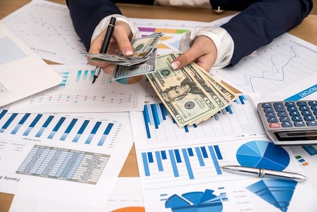 ビジネスレディはドルを数え、グラフィックをチェックします