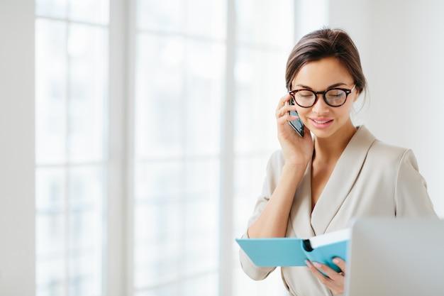 ビジネスの女性は、スマートフォンを介してパートナーと作業スケジュールについて説明します