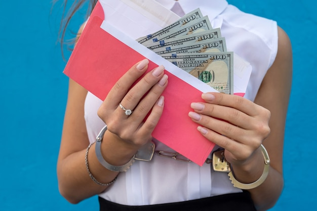 Business lady in handcuffs holding an envelope with dollars. concept of bribery and corruption