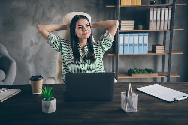 Бизнес-леди держаться за руки за головой, смотреть сбоку, мечта в офисе