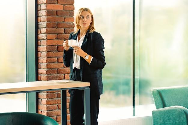 横を見てコーヒーのカップを保持しているビジネスの女性。オフィスの窓に立っている若いエレガントな金髪。スタートアップビジネスのマネージャーは、笑顔でコーヒーティーブレイクタイムをお楽しみください。