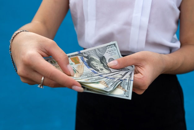 Business lady holding a lot of dollars isolated on a blue background. financial concept