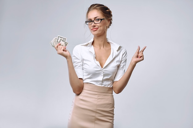 A business lady holds a little money in her right hand