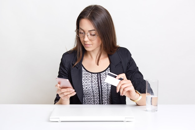 Business lady holds plastic card and smart phone, makes payment on store website, checks balance, types number on mobile phone, wears transparent glasses and black jacket, drinks water