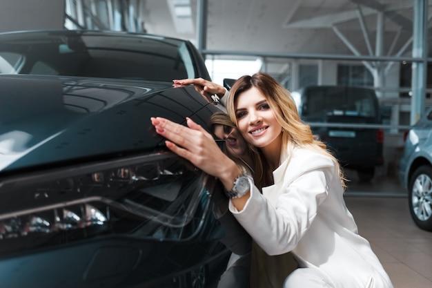비즈니스 여자는 그녀의 새 차를 안 아.
