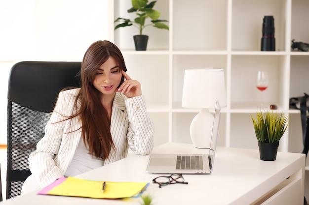 테이블에 앉아 가벼운 재킷에 비즈니스 레이디 노트북이 있습니다.