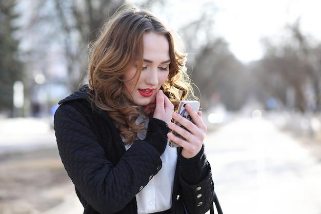 Бизнес-леди в костюме на открытом воздухе с мобильным телефоном