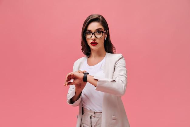 Бизнес-леди в очках смотрит на часы на розовом фоне. красивая серьезная девушка с красными губами в бежевом стильном костюме позирует.