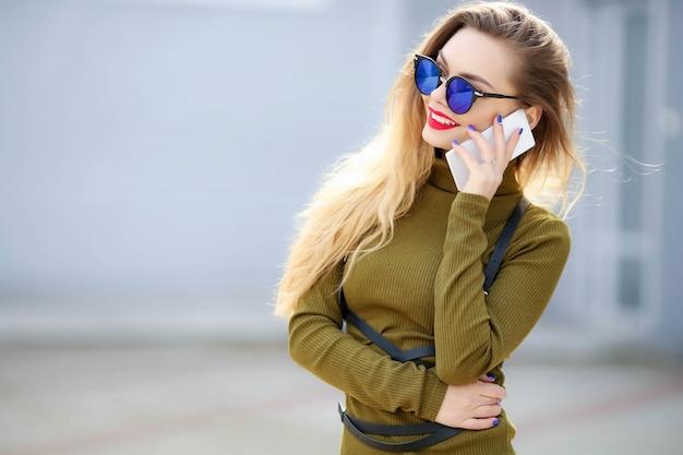 路上でスタイリッシュな服で電話でメガネの女性のビジネス。