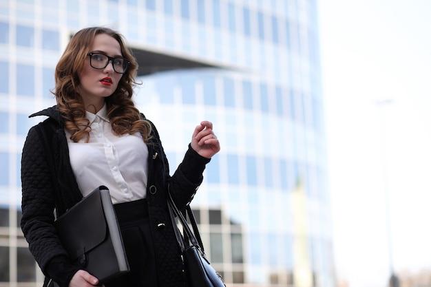 Бизнес-леди в строгой одежде на фоне зданий