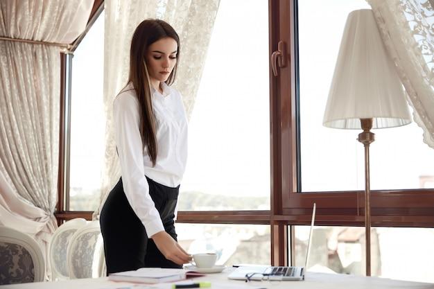 ビジネスの女性は、レストランで彼女の職場でコーヒーカップを保持しています。