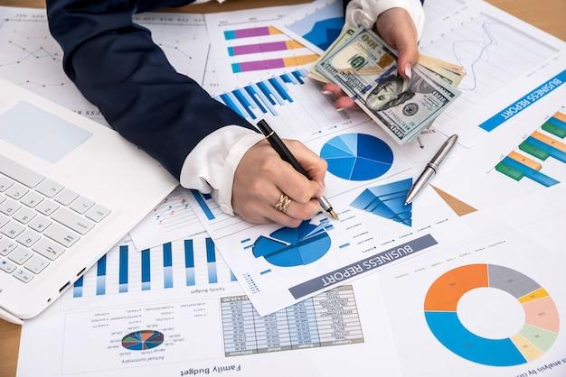 비즈니스 레이디 노트북 및 비즈니스 그래프와 함께 미국 달러를 손에 들고있다