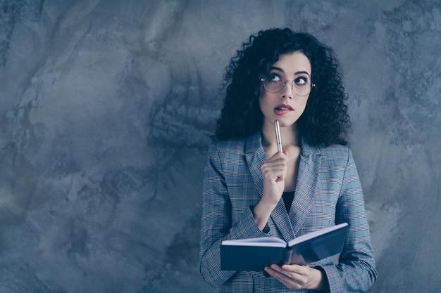 メモを作るビジネスの女性は灰色の壁に孤立していると思います