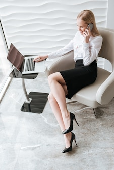 Business lady in office using laptop and talking by phone