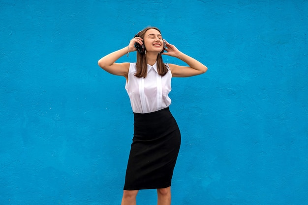비즈니스 여성은 직장에서 커피를 마시고 파란색으로 격리된 음악을 들으며 일시 중지합니다.