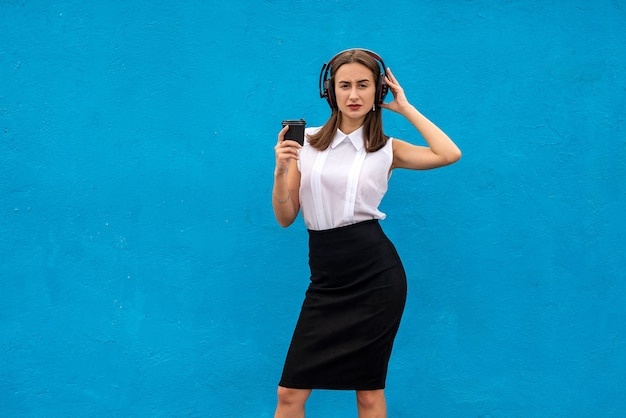 Business lady pauses at work drinking coffee and listening to music isolated on blue