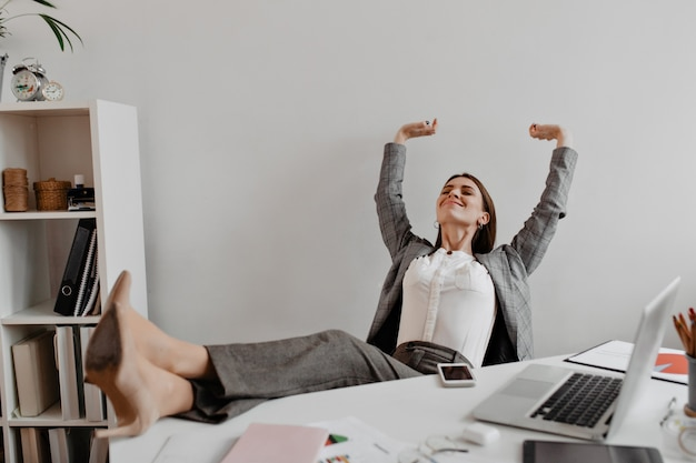 Business lady satisfied with working result with pleasure threw her legs to white desktop.