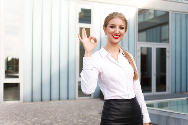 ビジネスの女性はokのジェスチャーを示しています。若いサラリーマンは指大丈夫ジェスチャーを示しています