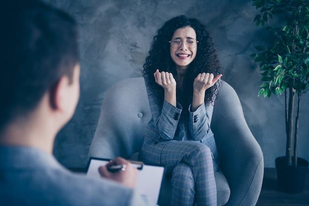비즈니스 아가씨 콘크리트 벽 배경에 의사 심리학자에게 울고 의자에 앉아