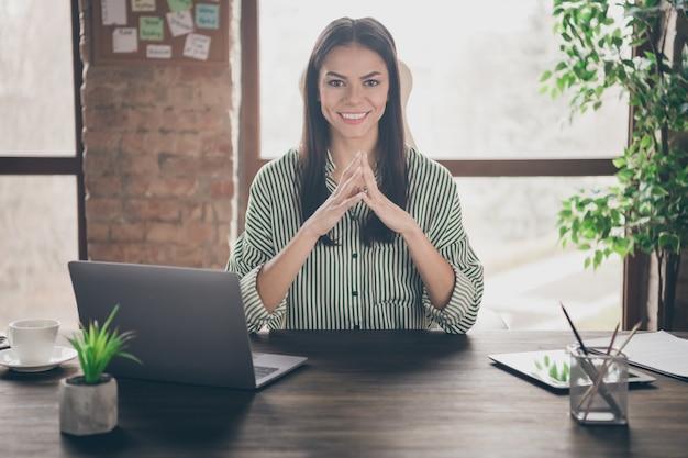Бизнес-леди сидит за столом в офисе на чердаке, держа пальцы