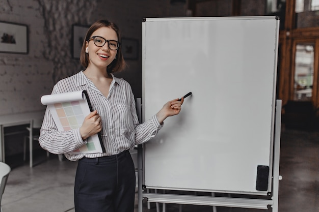 Business lady in strict suit and glasses smiles, holds documents and points to white office board.