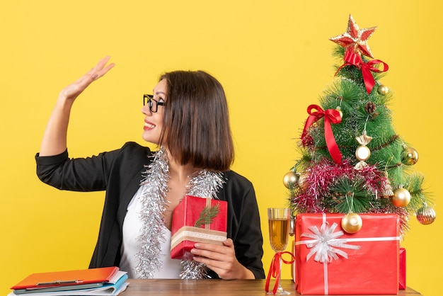Signora di affari in vestito con gli occhiali che tiene il suo regalo e dicendo ciao seduto a un tavolo con un albero di natale su di esso in ufficio