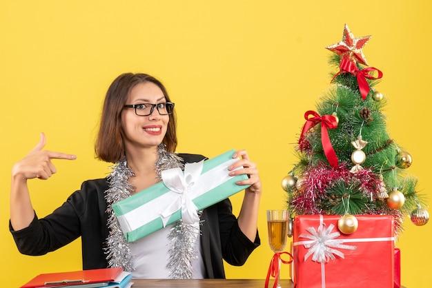 Signora di affari in vestito con gli occhiali che indica il suo regalo e che si siede a un tavolo con un albero di natale su di esso in ufficio