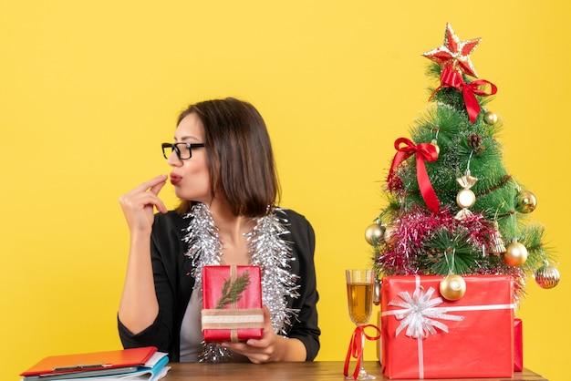 Signora di affari in vestito con gli occhiali che mostra il suo regalo chiudendo gli occhi e sognando e seduto a un tavolo con un albero di natale su di esso in ufficio