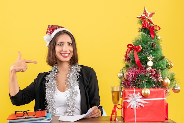 Business lady in suit with santa claus hat and new year decorations pointing herself and sitting at a table with a xsmas tree on it in the office