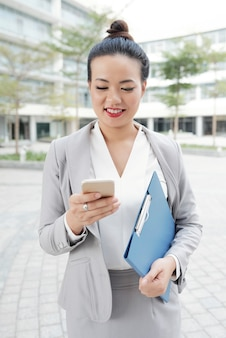 Business lady texting on smartphone