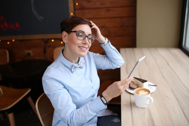 レストランで昼休み中にコーヒーのカップを持つ女性のビジネス