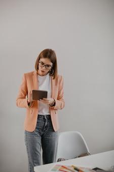 タブレットを興奮して見ている眼鏡をかけたビジネスレディ。白いオフィスでスタイリッシュな服装の若いマネージャーの肖像画。