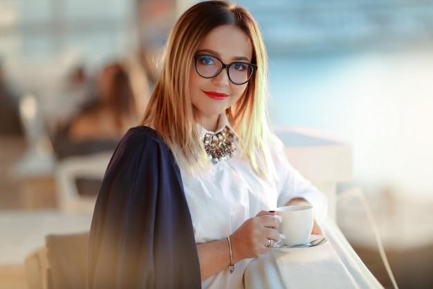 眼鏡と一杯のコーヒーまたはラップトップを手に持つ大人の女性のラップトップを持つビジネス女性