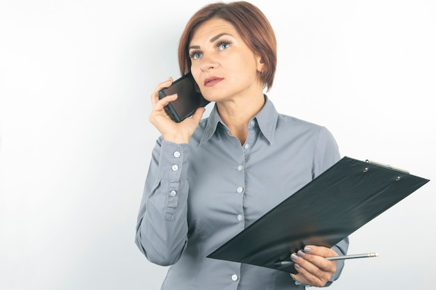 Business lady with phone and documents in hands on white wall.
