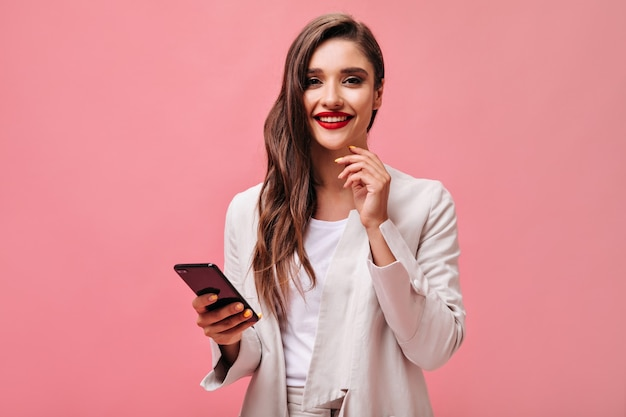 Business lady with red lips holds phone on pink background.  curly brunette in office attire is smiling and looking at camera.