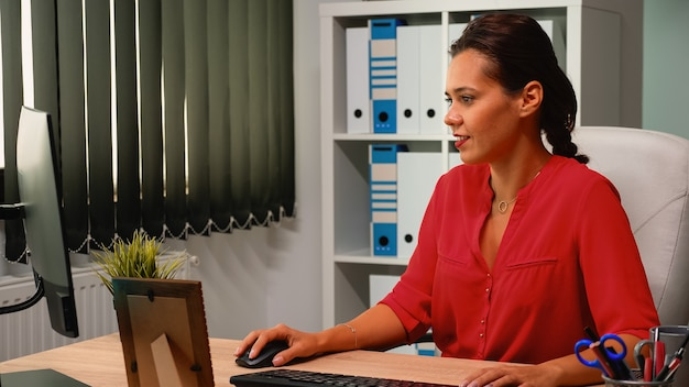 Business lady working alone at job on computer in office modern room. hispanic entrepreneur sitting in professional company workspace typing on pc keyboard looking at desktop reading reports
