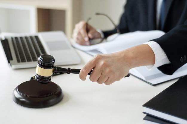 비즈니스 변호사 손을 노트북, 책 및 문서와 함께 사무실에서 정의 망치를 들고. 프리미엄 사진