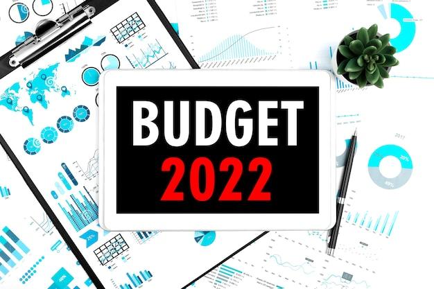 ビジネスレイアウト。タブレット上のテキスト予算2022。チャート、ドキュメント、グラフ用の植物、ペン、クリップボード。