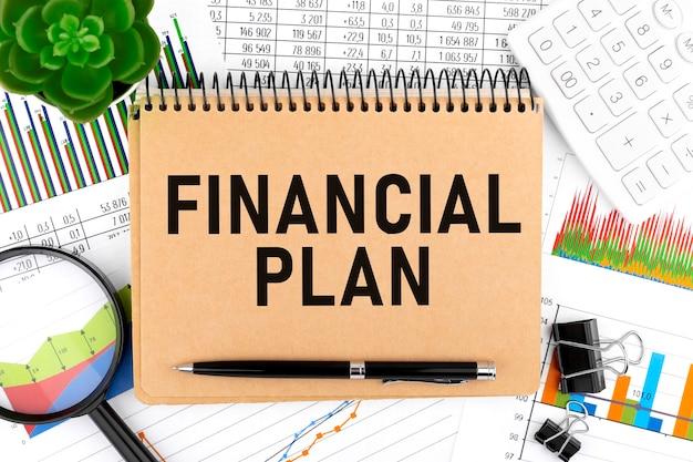 ビジネスレイアウト。ノートにfinancialplanとテキストを送信します。計算機、植物、ペン、拡大鏡、チャート、グラフ。