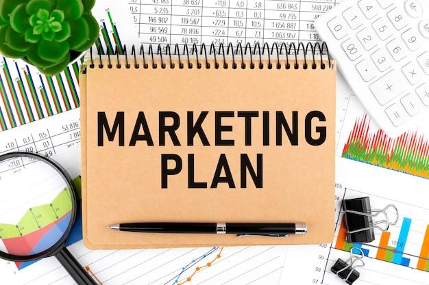 ビジネスレイアウト。ノートにマーケティング計画をテキスト送信します。計算機、植物、ペン、拡大鏡、チャート、グラフ。